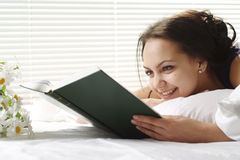 Lucky girl lies in bed reading a book Royalty Free Stock Image