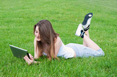 Lucky girl lying on grass with tablet. royalty free stock image