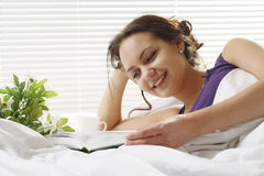 Lucky girl reading a book in bed Stock Photography