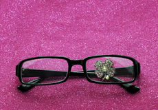 Lucky Glover Rhinestone Behind Eye Glasses. 4 Leaf lucky clover rhinestone sits behind the lens of a pair of eyeglasses Royalty Free Stock Photography