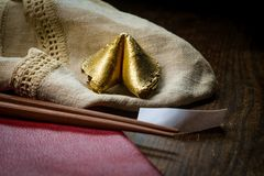 Lucky Golden Fortune Cookie. Lucky charm golden fortune cookie with chopsticks and dark moody lighting concept royalty free stock photos