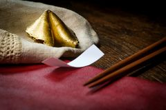 Lucky Golden Fortune Cookie. Lucky charm golden fortune cookie with chopsticks and dark moody lighting concept stock photo