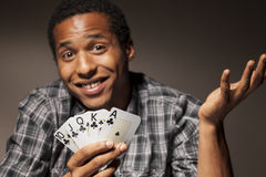 Lucky guy. Young man with compassion holds the winning poker cards Royalty Free Stock Photos