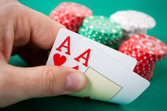 Lucky hand. Poker hand with two aces. Some casino chips in the background over a green gaming table Stock Photo