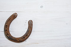 Lucky horseshoe, used with rust, on white painted wood, symbol f Stock Images