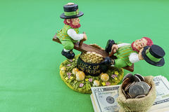 Lucky irish concept cash gold coins. Irish leprechauns luck playing on pot of gold and pile of banknotes paper cash money with bag of coins green background royalty free stock photos