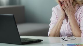 Lucky lady in her 50s reading winner list online, rejoicing her lottery victory