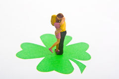 Lucky in Love. Miniature figures embracing on a four leaf clover Royalty Free Stock Photography