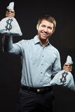Lucky man. Excited young man holding money bags on black background Stock Images