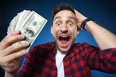 Lucky man holding 100 dollar bill money in his hand. Handsome bearded man in red shirt. Funny guy is a lucky winner, she is holding a pile of money, he is stock photography