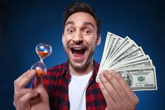 Lucky man holding 100 dollar bill money and hourglass in his hand. Handsome bearded man in red shirt with cash and Hourglass . Funny guy is a lucky winner, she royalty free stock photography