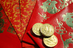 Lucky Money. Gold (chocolate) coins and red packets (lai see, filled with money), traditionally given by elders to younger people during Chinese New Year Stock Photos