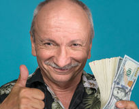 Lucky old man holding dollar bills Royalty Free Stock Images