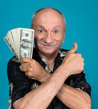 Lucky old man holding dollar bills. On a blue background Royalty Free Stock Photos