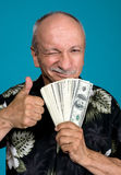 Lucky old man holding dollar bills. On a blue background Stock Images