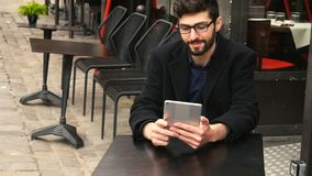 Online poker player using tablet at cafe table in slow motion. Lucky online poker player sitting at cafe table with tablet enjoying with game in slow motion stock footage