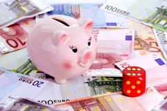 Lucky Pig. Piggy bank and dice on Euro notes royalty free stock image