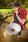 Lucky prospector testing purity of gold nugget Stock Image