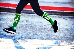 Lucky runner - legs and feet of marathon jogger in St Patrick`s Day race with green lucky socks stock photography