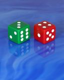 Lucky Seven. Red and green dice mirror image on blue glass tile Royalty Free Stock Image