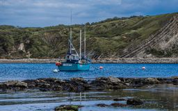 Lulworth cove fishing boat at rest royalty free stock images