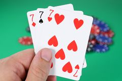 Lucky Sevens. Hand of three lucky sevens royalty free stock photo
