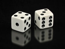 Lucky Sevens White Dice on Black Background. Two white dice with the lucky number seven showing. The dice are on a solid black background with a soft reflection Royalty Free Stock Photography