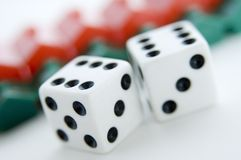 Lucky Sixes. Two dice show sixes in front of a row of plastic houses (shallow depth of field used Stock Photography