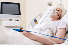 Lucky sore lady being treated using specialized equipment. Clinical condition. Delicate ill aged woman resting in hospital bed while recovering from illness and Stock Photography
