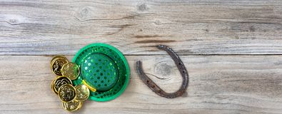 Lucky St Patrick objects on rustic wooden board background. Lucky green hat, horseshoe and gold coins for St Patrick on rustic wooden boards in overhead view Stock Images