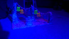 Lucky Star~ Rainbow Neon Blacklight. Handcrafted. Rainbow pillars, dripping paint. Tiny neon-coloured glass cups hanging on Pastel&NeonPink wool threads attached stock photo
