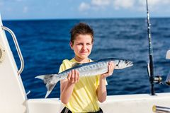 Boy deep sea fishing. Lucky teenage boy holding barracuda proud with the catch on boat deck Stock Images