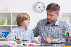 Lucky to have such a supportive dad. Shot of a little boy listening to his father while doing homework Stock Image