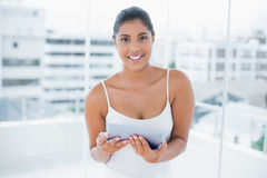 Lucky toned brunette using tablet Stock Photography