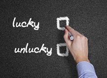 Lucky and unlucky handwritten with white chalk black background. Or blackboard Royalty Free Stock Photos