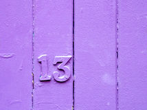 Lucky or unlucky. Number thirteen on purple  painted wooden fence Royalty Free Stock Photo