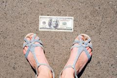 Lucky woman finding money on the street. Women feet next to hundred dollar bill. Lost and found money lying down on Stock Photos