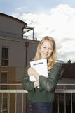 Lucky woman with tenancy agreement. Young woman on the balcony hugs her tenancy agreement Stock Photography