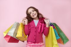Lucky young long-haired girl holding in hands lot of colorful shopping bags with shopping with a satisfied expression on her face Royalty Free Stock Image