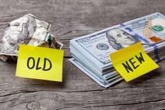 Lucre com o negócio velho e novo, conceito Etiquetas do escritório na cédula e na pilha amolgadas dos dólares Fotos de Stock Royalty Free