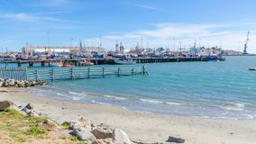 Luderitz,纳米比亚- 2014年7月08日:Luderitz海滩和港口与许多fishings小船的在晴天 免版税库存图片