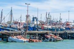 Luderitz, Namibia - 8 de julio de 2014: Puerto de Luderitz con muchos barcos de pesca y un naufragio hundido imagen de archivo libre de regalías