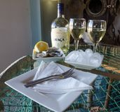 Luderitz, Namibia - July 08 2014: Fresh oysters, ice and white wine, white plates on glass table, Shearwater Oyster Bar. Luderitz, Namibia - July 08 2014: Fresh Royalty Free Stock Image