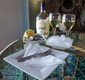 Luderitz Namibia, Lipiec, - 08 2014: Świeże ostrygi, lód i biały wino, biali talerze na szkło stole, Shearwater Ostrygowy bar Obraz Royalty Free