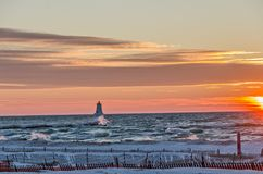 North Breakwater Lighthouse with Ice. Ludington, Michigan`s North Breakwater Light with a beautiful sunset and blue green waves with whitecaps crashing in to the royalty free stock images