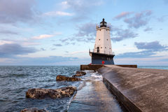 Ludington Pier Lighthouse in Early Morning. The North Breakwater Pier Lighthouse in Ludington Michigan rises above Lake Michigan with an early morning sky royalty free stock image