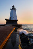 Ludington Pier Lighthouse at Sunset - Michigan. The Ludington Light reflects in a pool of water on the North Breakwater Pier. The North Breakwater not only is stock photo