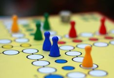 Ludo. Board game Ludo - colored figurines and dice on a board Stock Photography
