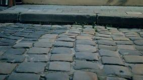 Ludzcy cieki w butach chodzą na kamiennej drodze miasta odprowadzenie zbiory