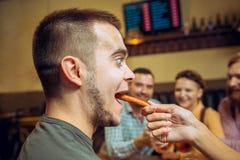 Ludzi, czasu wolnego, przyjaźni i komunikaci pojęcie, - szczęśliwi przyjaciele pije piwa, opowiadać i clinking szkła, przy barem zdjęcia stock